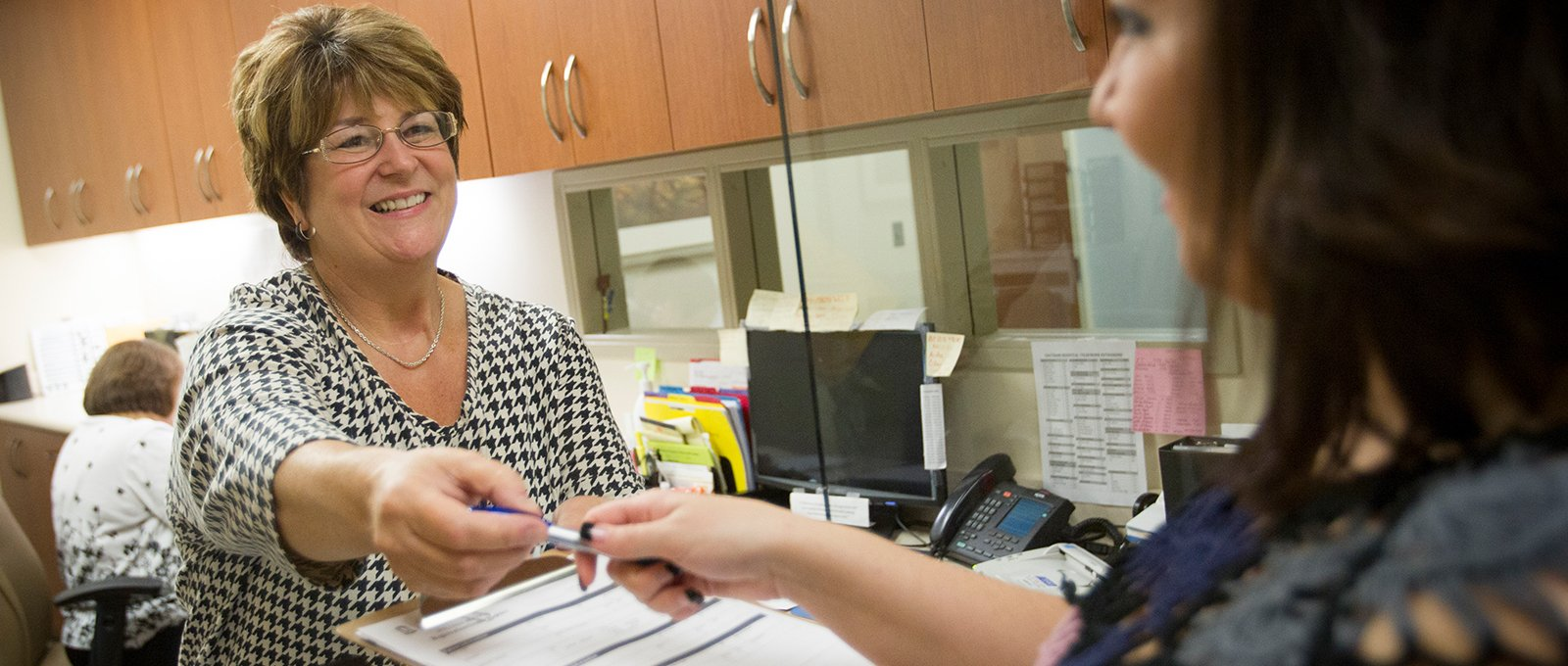 Smiling staff member hands patient form to patient