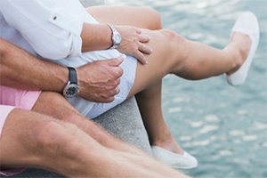 older couple sitting on dock, focus is on their legs