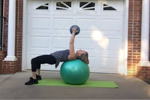 Rex Wellness Trainer Vicky works out on exercise ball in home driveway