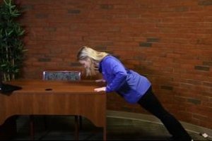 Woman doing push-ups against an office desk