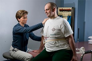 Female physician touching a seated male patient's shoulder and back.